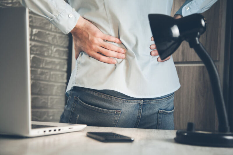 A businessman reaching his back due to low back pain